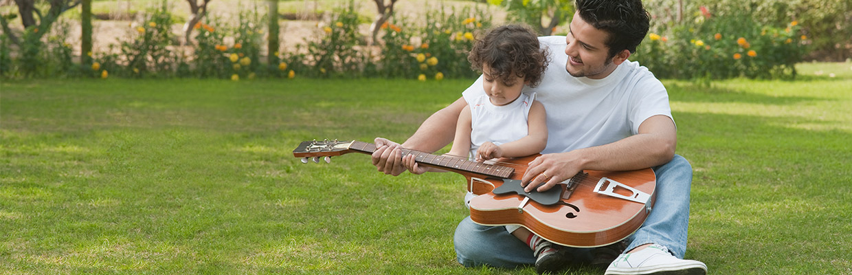 A father is teaching his kid playing guitar; image used for HSBC NRE rupee term deposit.