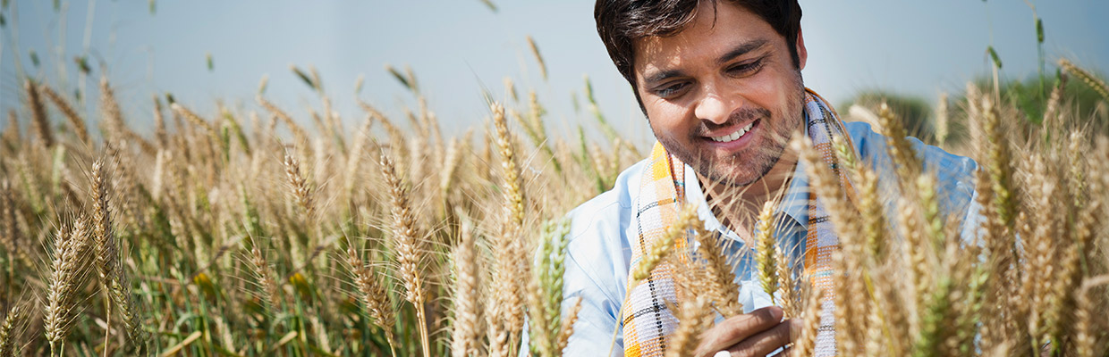 A farmer smiling in the field; image used for HSBC investments page.