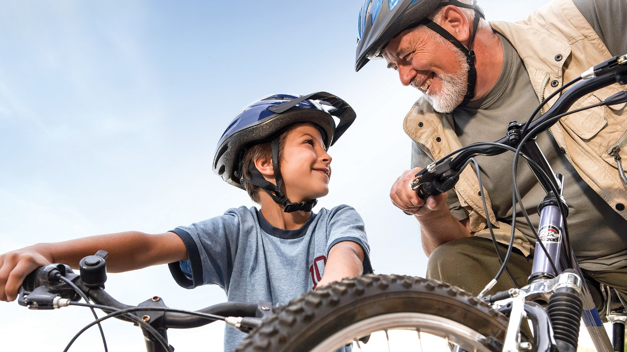 A grandpa and his grandchild are riding bikes; image used for HSBC mutual funds page.
