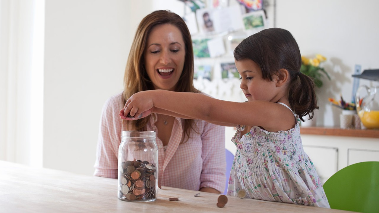 Mother and daughter filling a piggy bank; image used for HSBC Basic Savings Account page.