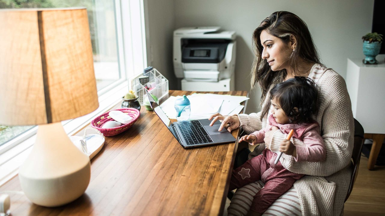 Mother multi-tasking with infant daughter in the living room; image used for HSBC Smart Home Loan page