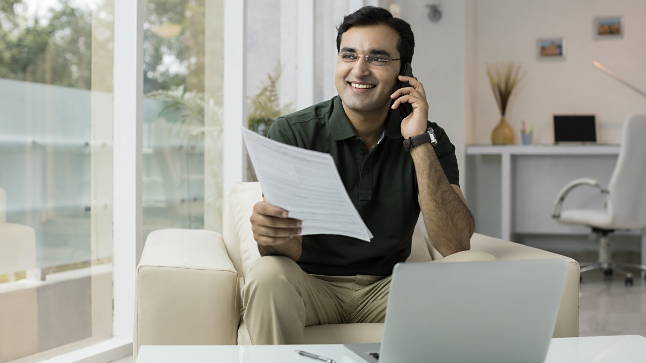 A man holding document and talking over the phone happily; image used for HSBC NRE rupee account page