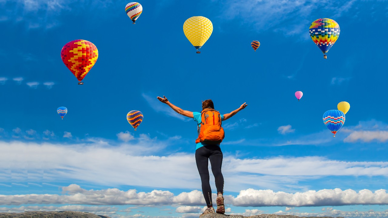 A woman with backpack looking up the hot air balloons in the sky; image used for HSBC India Premier emergency services page