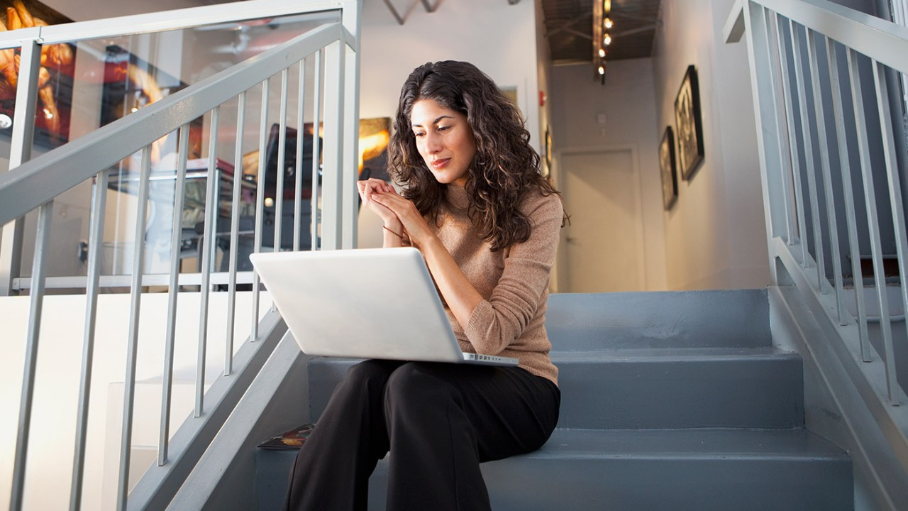 A woman is sitting on stairs with a laptop; image used for HSBC Demat account page.