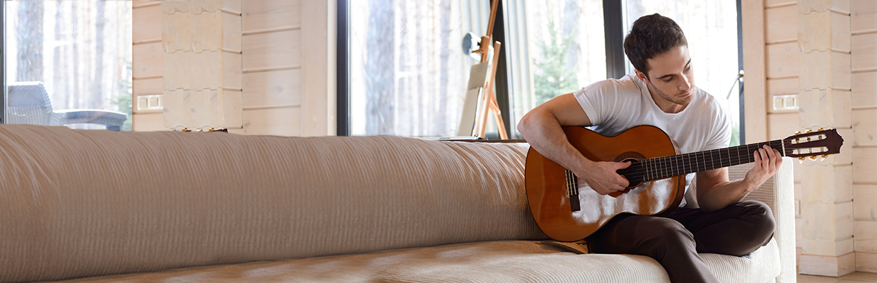 A man playing guitar at home; image used for HSBC India credit card features Cash-on-EMI page