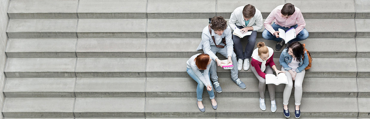 A group of teenagers are sitting together on the stairs; image used for HSBC Looking to study in Canada
