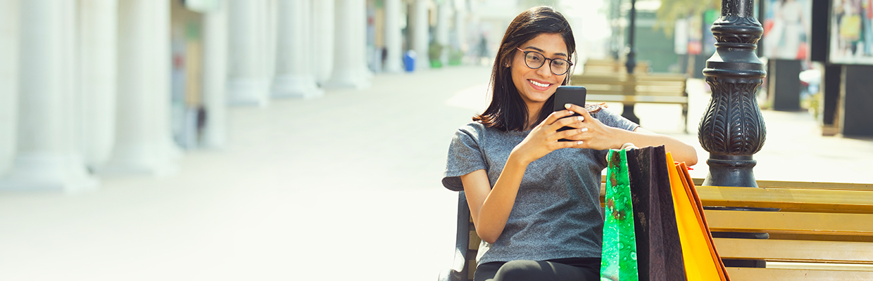 A woman sitting on bench and playing with her mobile phone; image used for HSBC Balance Conversion.